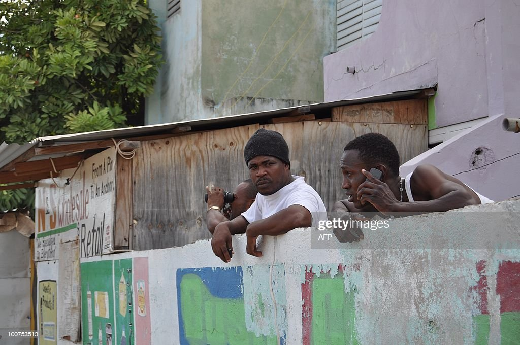 Residents follow street battles in the Trench Town neighborhood of Kingston, Jamaica May 24, 2010. Gun battles raging in the Jamaican capital have left more than 60 people dead, mostly civilians, hospital sources said May 25, as troops fanned out across the city hunting an alleged drug kingpin. Hundreds of troops and police have been deployed to hunt down Christopher 'Dudus' Coke, wanted in the United States on drug-trafficking charges, amid a week-long standoff with his loyal supporters. AFP PHOTO / Ratiba HAMZAOUI