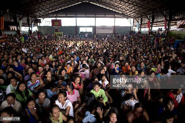 Residents from the slum area of Baseco Tondo in Manila wait at the start of a gift giving program by former Philippine President and Manila Mayor...