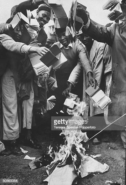Black South Africans during a race riot in buring African pass books