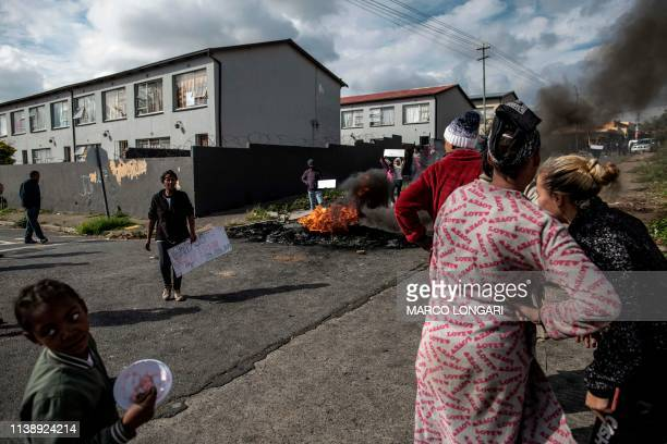 TOPSHOT Residents gather around a burning tyre in the street of Johannesburg on April 23 2019 during a protest against the lack of service delivery...