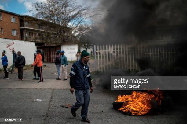 Residents gather around a burning tyre in the street of Johannesburg on April 23 2019 during a protest against the lack of service delivery or basic...