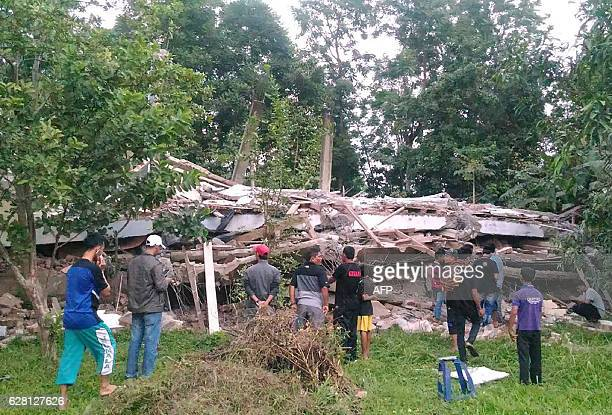 Residents gather around a collapsed building after a 65magnitude earthquake struck the town of Pidie Indonesia's Aceh province in northern Sumatra on...