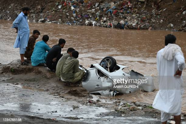 Residents gather as they look at a damaged car submerged in flood waters after heavy monsoon rains in Islamabad on July 28, 2021.