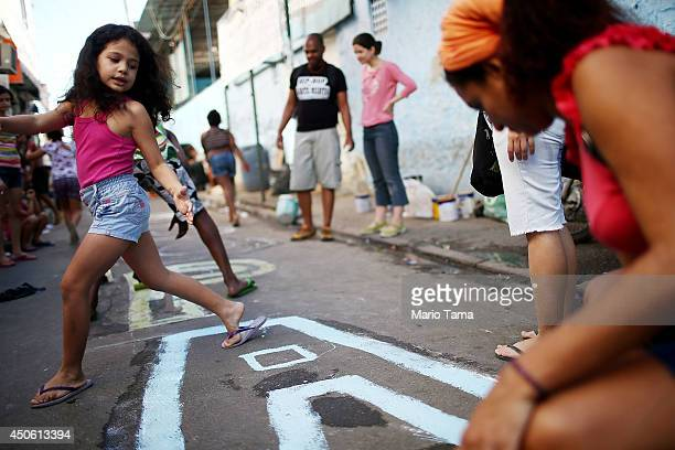 Residents gather at a demonstration where protestors painted a street with the phrase 'Cup for Whom' in the Mare community or 'favela' on June 14...