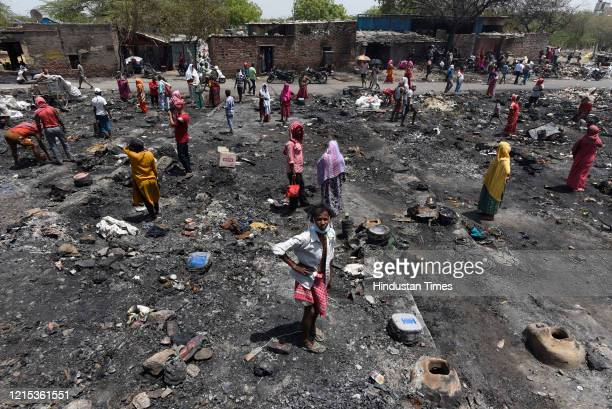 Residents gather at the fire site in which around 1000 shanties burnt down and turned into ashes on Monday night at Tughlakabad Extension on May 26...