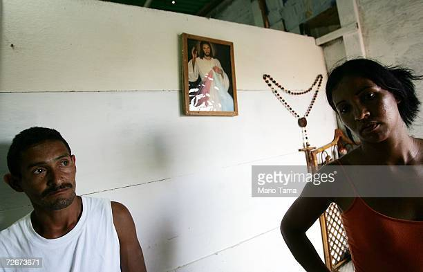 Residents gather in the poor barrio of Coche beneath a portrait of Jesus November 29 2006 in Caracas Venezuela Despite daily problems with fresh...