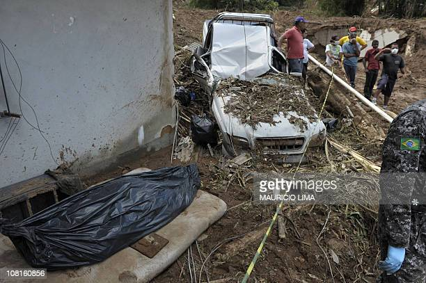 Residents gather near a destroyed vehicle and a bodybag with the corpse of a man found at the scene of a recent landslide where seven people were...