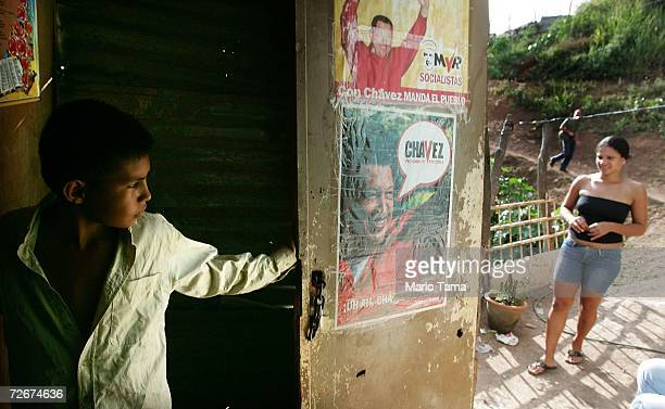 Residents gather next to Chavez posters in the poor barrio of Coche November 29 2006 in Caracas Venezuela Despite daily problems with fresh water and...