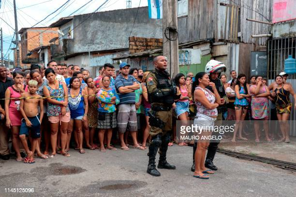 Residents gather outside a bar as forensic personnel and criminal police remove corpses after a shooting in Belem Para state Brazil on May 19 2019 At...