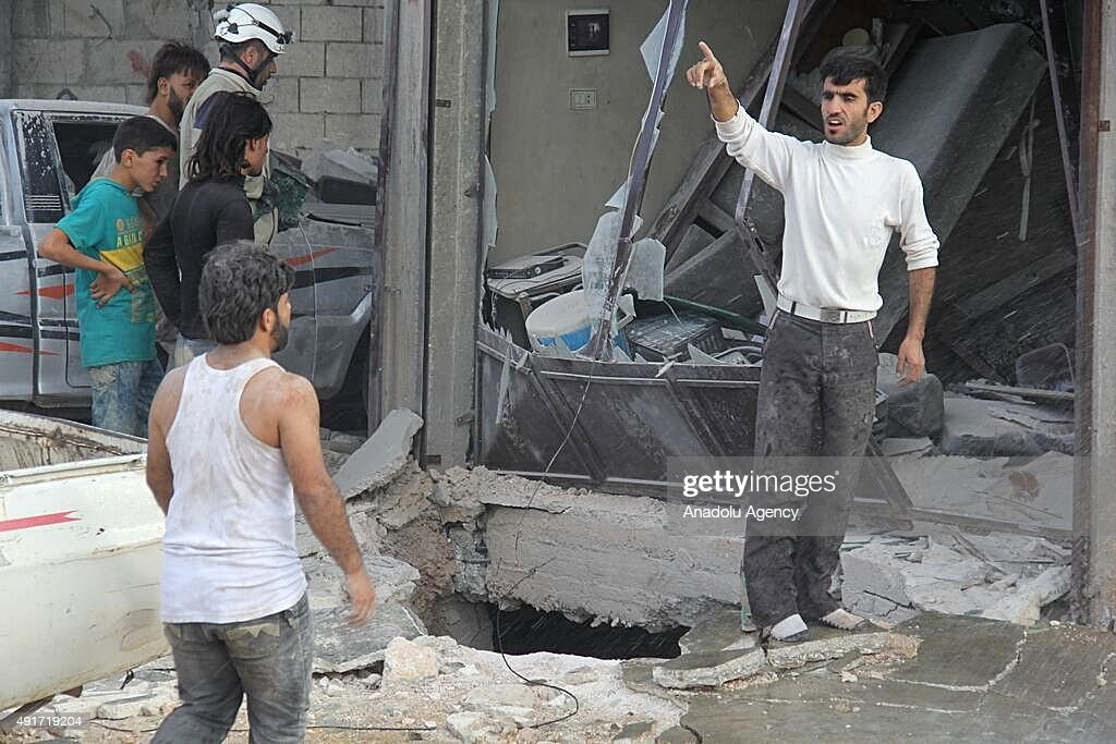 Residents gather outside the destroyed buildings after Russian air strikes in Maasaran town, Idlib, Syria on October 07, 2015.