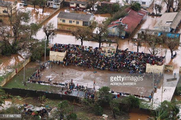 Residents gather stranded on the stands of a stadium in a flooded area of Buzi, central Mozambique, on March 20 after the passage of cyclone Idai. -...