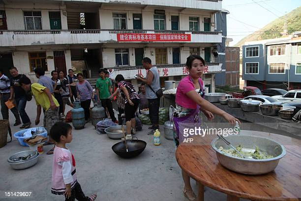 Residents gather to cook a meal in Yiliang, southwest China's Yunnan province on September 7 following two shallow quakes that struck the remote and...