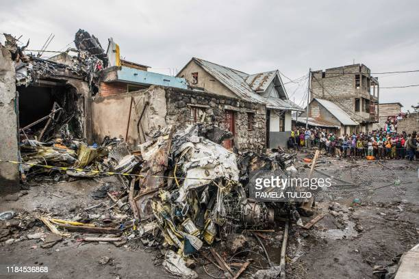 Residents gather to look at the wreckage of a small aircraft that crashed on November 24 in a densely populated area is seen in Goma on the East of...