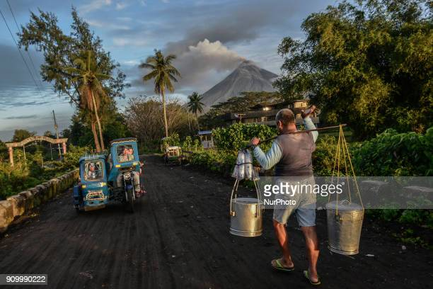 Residents go about daily life as Mount Mayon makes a mild eruption as seen from Daraga Albay province Philippines January 25 2018 Mount Mayon the...