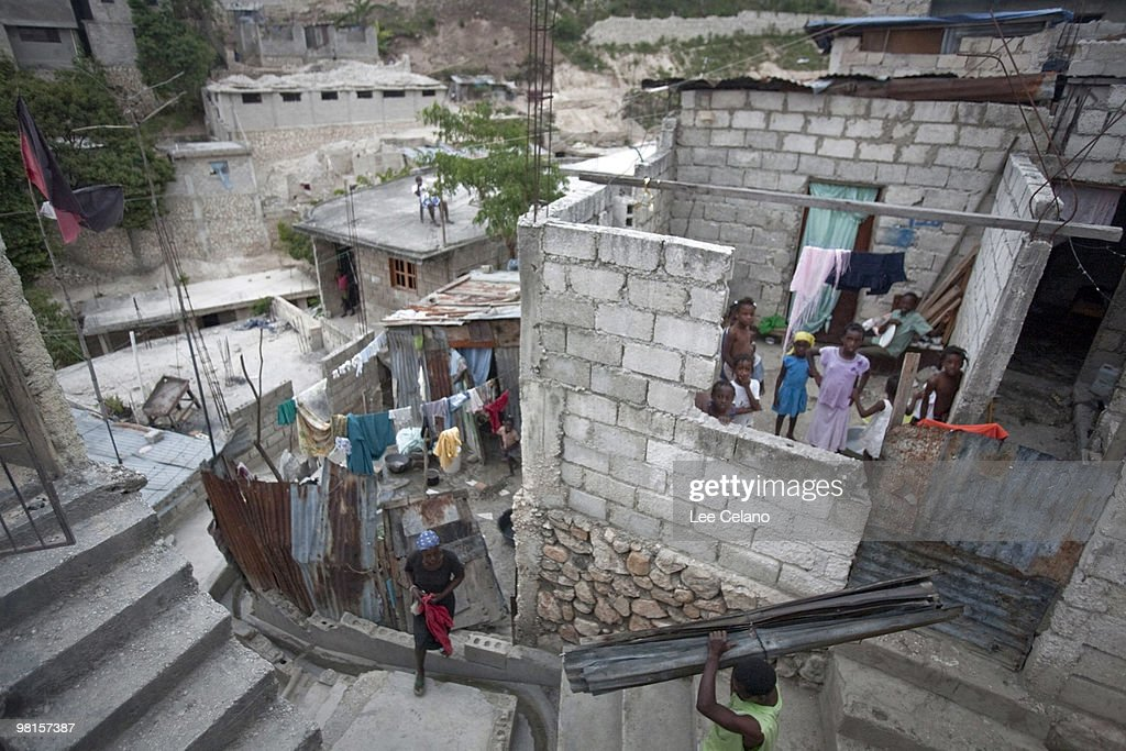 Residents go about life amid earthquake-damaged buildings March 30 2010 in the Peguy & Rebuilding Efforts Too Slow For Thousands Of Haitians In Tent ...