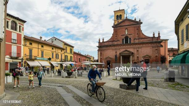 Residents go about their activities across Piazza XX Settembre past San Biagio and Santa Maria Immacolata church on May 20, 2020 in Codogno,...