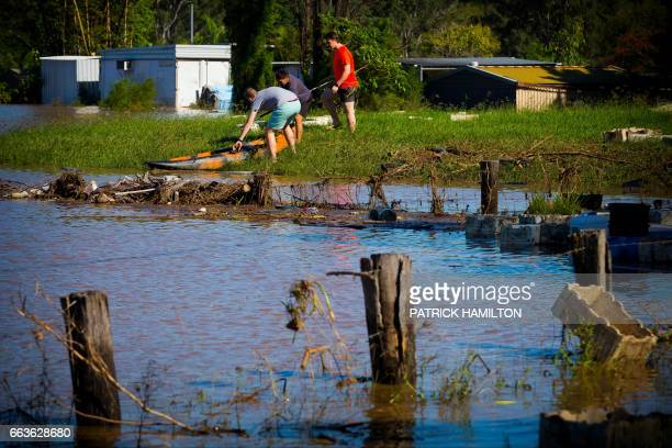 Residents handle a kyack as floodwaters caused by Cyclone Debbie recede in the town of Beenleigh on April 2 2017 Rising floods continued to plague...