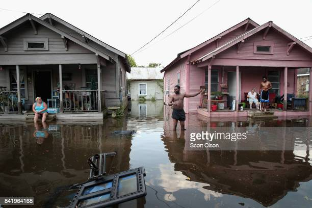 Residents hang out in front of their homes which are surrounded by floodwater after torrential rains pounded Southeast Texas following Hurricane and...