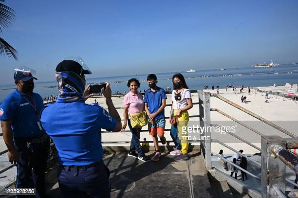 Residents have their photos taken at a footbridge overlooking the Manila baywalk dolomite beach along Roxas boulevard in Manila city on October 17 a...