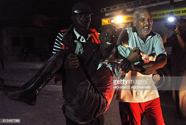 Residents help a man wounded during an attack in the center of Mogadishu on February 26 2016 Two loud explosions rocked the centre of Mogadishu today...
