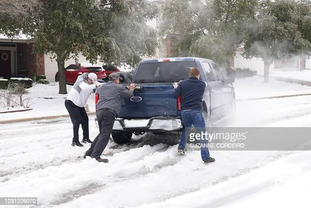 Residents help a pickup driver get out of ice on the road in Round Rock, Texas, on February 17 after a winter storm. - Millions of people were still...