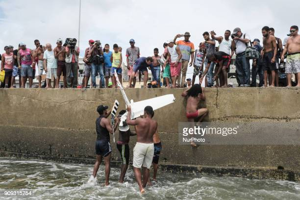 Residents help firefighters and rescue a part of the helicopter's propeller in Recife Northeast Brazil on January 23 2018 A helicopter from the Globo...