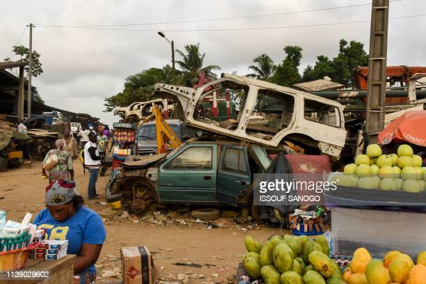 Residents hold a market amongst piles of destroyed vehicles in the Adjame neighborhood of Abidjan on April 23 2019 The Ivorian authorities plan to...