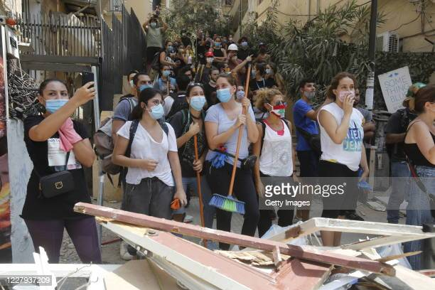 Residents hold brooms as they protest government negligence, allegedly behind Tuesdays explosion, on August 6, 2020 in Beirut, Lebanon. On Thursday,...
