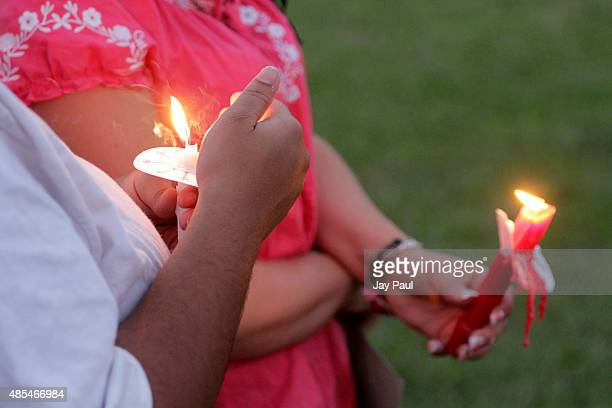 Residents hold candles during a vigil for Alison Parker on Martinsville High School's football field on August 27 2015 in Martinsville Virginia Two...
