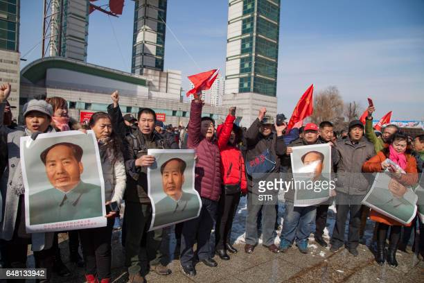 Residents hold posters of late communist leader Mao Zedong during a protest calling for a boycott of South Korean goods in Jilin in China's northeast...