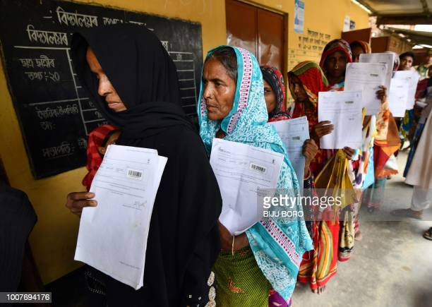 Residents hold their documents as they stand in a queue to check their names on the final list of National Register of Citizens at a NRC Sewa Kendra...
