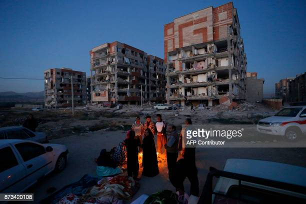 TOPSHOT Residents huddle by a fire in an open area following a 73magnitude earthquake at Sarpole Zahab in Iran's Kermanshah province on November 13...