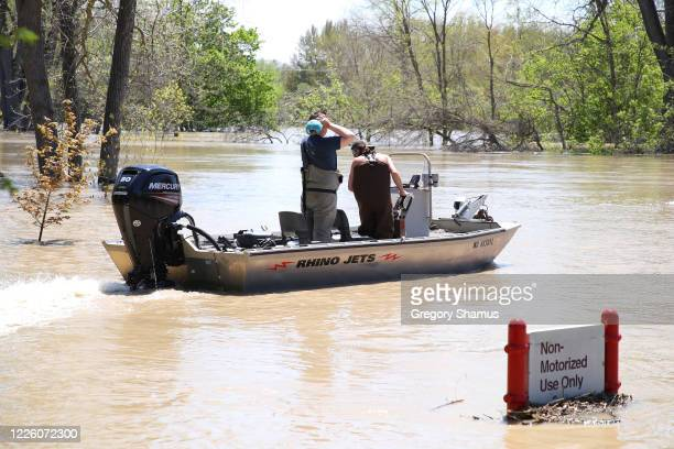 Residents in a boat inspect the floodwaters flowing from the Tittabawassee River into the lower part of downtown on May 20, 2020 in Midland,...