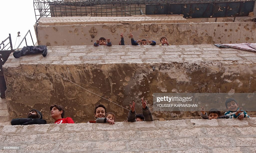 TOPSHOT - Residents in a government-held part of Aleppo's Salaheddin neighbourhood look out from the balconies of their damaged houses at the road on which the convoy evacuating civilians and rebel fighters from the last rebel-held neighbourhood in the northern Syrian city were supposed to pass on December 16, 2016. The Syrian government suspended the evacuation of civilians and fighters from the last rebel-held parts of Aleppo on Friday, leaving thousands of people trapped and uncertain of their fate. / AFP / Youssef KARWASHAN
