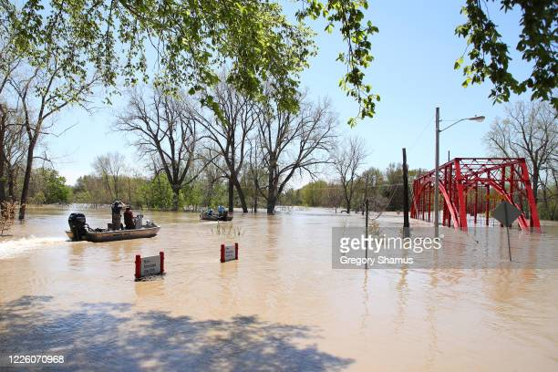 Residents in boats inspect the floodwaters flowing from the Tittabawassee River into the lower part of downtown on May 20, 2020 in Midland, Michigan....