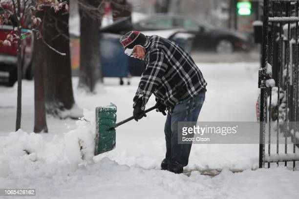 Residents in Humboldt Park dig out after an early winter snowstorm dumped several inches snow on the neighborhood on November 26 2018 in Chicago...