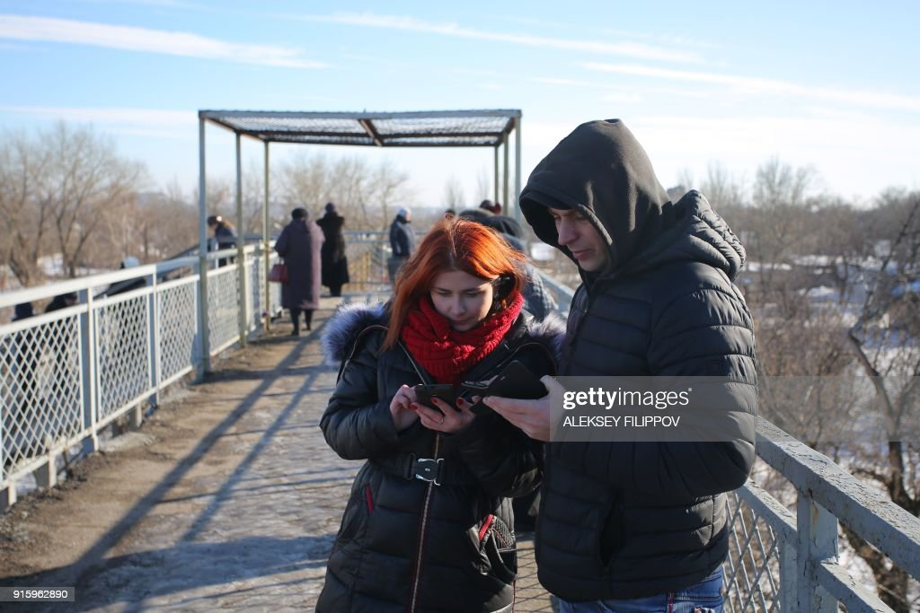 Residents in the hope of catching a signal from cell towers make their calls from a bridge, one of the few places available for mobile connection provided by Vodafone Ukraine (former MTS) in Donetsk on February 2, 2018. Every day dozens of people in the Ukrainian rebel stronghold of Donetsk gather on a windswept railroad overpass not far from the frontline despite the risk of coming under fire. They come to the bridge at a half-abandoned railway station on the outskirts of the city in the hope of catching a signal from cell towers on the other side of the frontline to be able to call their family and friends in government-controlled territories. PHOTO / Aleksey FILIPPOV