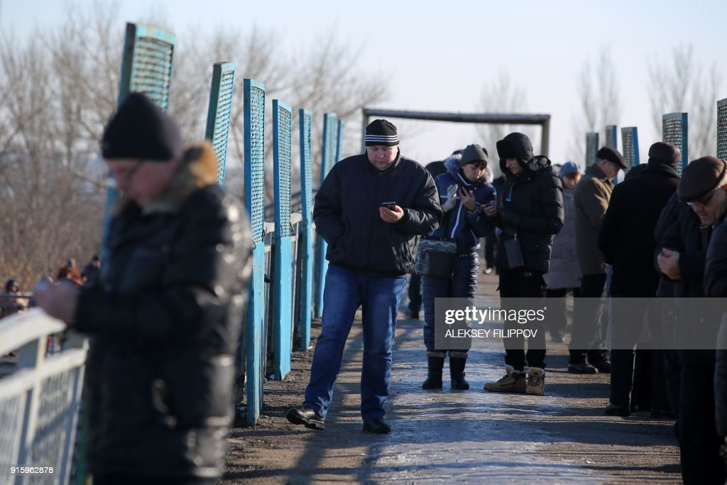 Residents in the hope of catching a signal from cell towers make their call on a bridge, one of the few places available for mobile connection provided by Vodafone Ukraine (former MTS) in Donetsk on February 2, 2018. Every day dozens of people in the Ukrainian rebel stronghold of Donetsk gather on a windswept railroad overpass not far from the frontline despite the risk of coming under fire. They come to the bridge at a half-abandoned railway station on the outskirts of the city in the hope of catching a signal from cell towers on the other side of the frontline to be able to call their family and friends in government-controlled territories. PHOTO / Aleksey FILIPPOV
