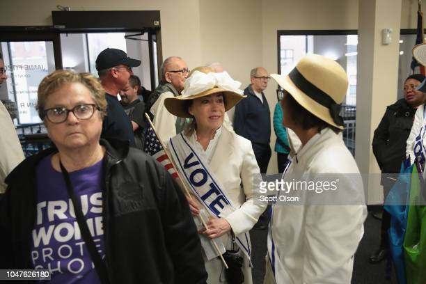Residents including Women dressed as suffragettes wait in line to receive a ballot for the midterm elections at the Polk County Election Office on...