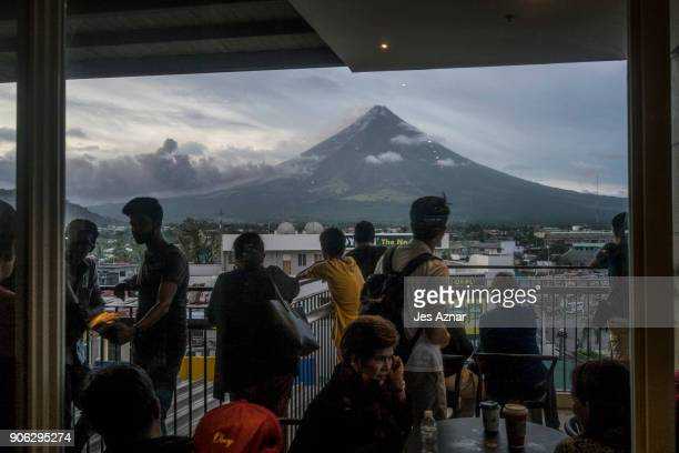 Residents inside a mall view and take pictures of Mayon volcano as it spews ash and lava on January 17 2018 in Legazpi Albay Philippines Thousands...