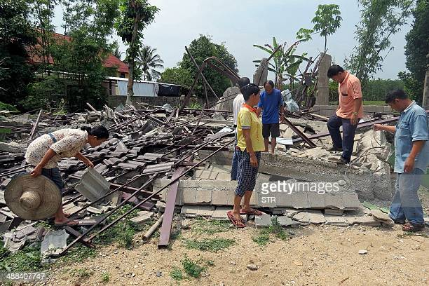 Residents inspect a flattened building a day after a 60magnitude quake struck in Thailand's northern province of Chiang Rai on May 6 2014 An elderly...