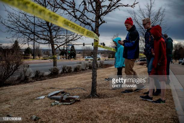 Residents inspect damage from debris fallen from a United Airlines airplane's engine in the neighborhood of Broomfield, outside Denver, Colorado, on...