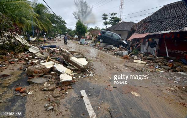 TOPSHOT Residents inspect damaged buildings in Carita on December 23 after the area was hit by a tsunami on December 22 following an eruption of the...