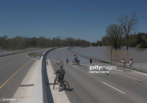Residents inspect the floodwaters flowing from the Tittabawassee River into the lower part of downtown on May 20, 2020 in Midland, Michigan....