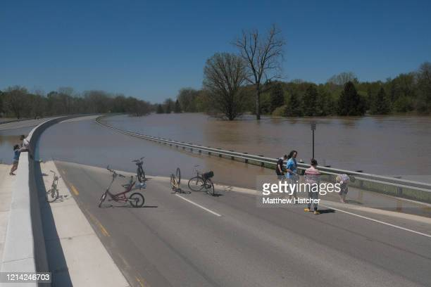 Residents inspect the floodwaters flowing from the Tittabawassee River into the lower part of downtown on May 20 2020 in Midland Michigan Thousands...