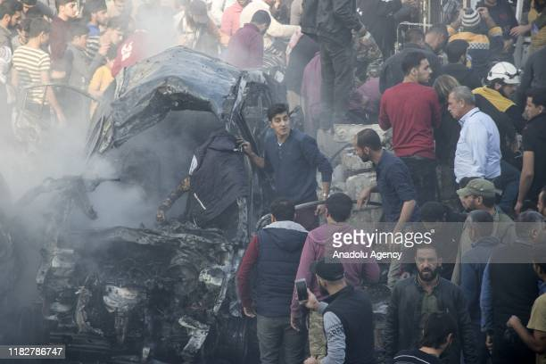 Residents inspect the scene of the attacks came from two bombladen vehicles in alBab district in Syria on November 16 2019 At least 10 civilians were...