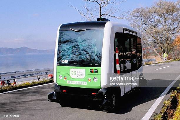 Residents join the nation's first demonstration experiment of a selfdriving bus on a public road on the bank of Lake Tazawako on November 13 2016 in...