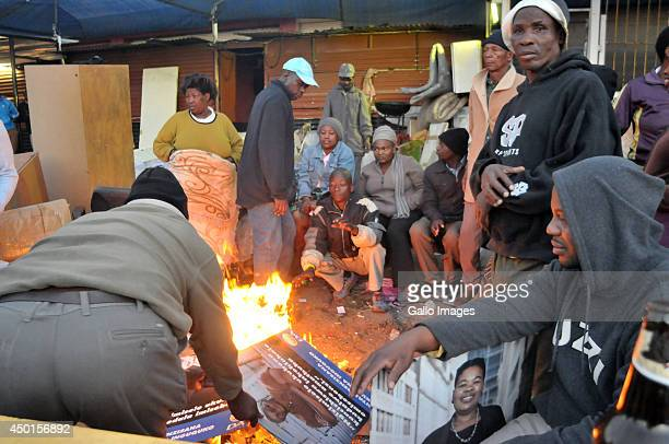Residents keep warm with a makeshift fire made of DA Electiosn posters on June 5 2014 in Alexandra Township in Johannesburg South Africa Residents...