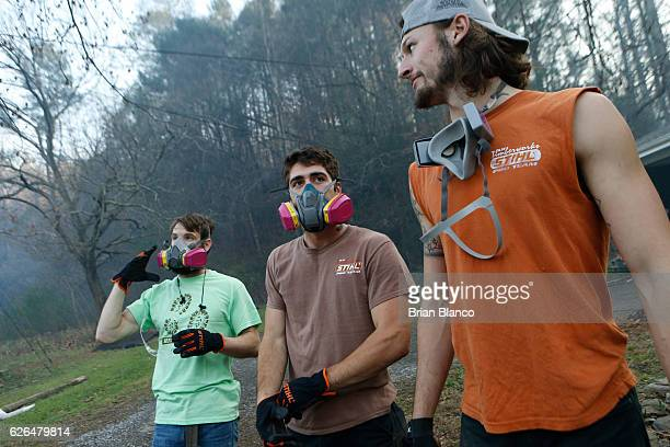 Residents Kirk Wallace Caleb Graves and Tyler Alden gather to clear debris and put out small fires near surrounding homes as the remains of their...