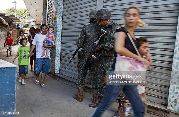 Residents leave their homes while Brazilian Army soldiers patrol the entrance to the Morro de Alemao shantytown on November 27 2010 in Rio de Janeiro...